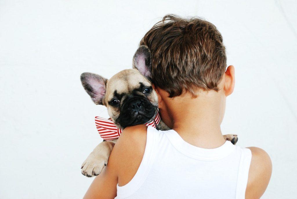 Boy hugging their pet dog